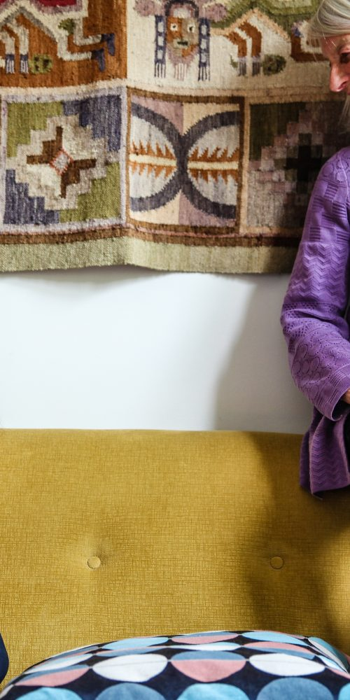 Two women dressed in different shades of purple relax on a mustard yellow sofa.